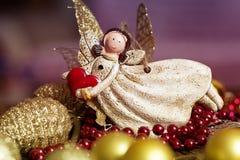 有心脏的天使玩具在手中在圣诞节背景 基督 免版税图库摄影