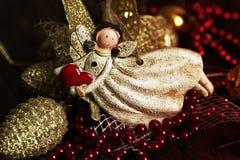 有心脏的天使玩具在手中在圣诞节背景 基督 库存照片