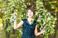 有心脏的小女孩 亚洲妇女微笑愉快在晴朗的夏天或春日外面在开花的树庭院里 相当 库存照片