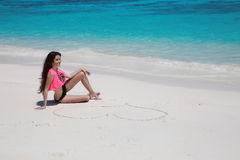 有心脏的性感的美丽的女孩在黑比基尼泳装放松的沙子 库存图片