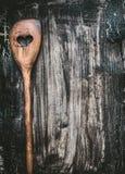 有心脏的木烹调匙子在黑暗的土气背景,顶视图 食谱的食物背景 免版税库存图片