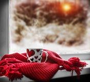 有心脏的杯在窗台在一个冬天的背景中 免版税图库摄影
