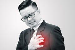 有心脏的症状的亚裔商人 库存图片