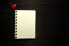 有心脏的空白的笔记本在黑背景 免版税库存图片