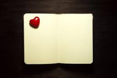 有心脏的空白的笔记本在黑背景 图库摄影