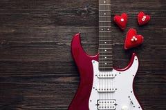 有心脏的红色电吉他在黑暗的木背景 温泉 免版税库存图片