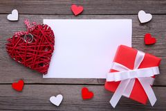 有心脏的红色礼物盒在灰色背景 免版税库存图片