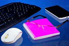 有必要的辅助部件的办公桌,蓝色背景 在重要纪录的桌面办公室笔记本上,智能手机 图库摄影