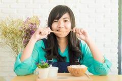 有快乐冰淇凌的看起来的愉快的亚裔女孩快乐和 免版税库存照片