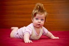 有快乐的发型的逗人喜爱的滑稽的女婴 免版税库存照片