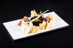 有快餐的一个广泛选择的一块大板材喜欢葡萄,乳酪,核桃,在黑暗的背景的薄脆饼干 免版税库存图片