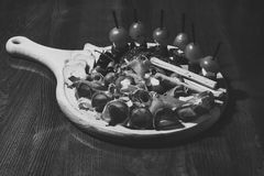 有快餐的委员会在木桌上 餐馆盘概念 冷的开胃菜用蕃茄,香肠,蒜味咸腊肠,火腿,芝麻菜 免版税库存图片