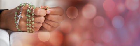 有念珠的手在圣经和红色bokeh转折 免版税库存图片