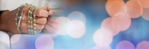 有念珠的手在圣经和蓝色橙色bokeh转折 库存图片