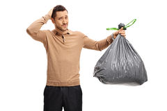 有怀疑地拿着他的头的垃圾袋的年轻人 免版税库存图片