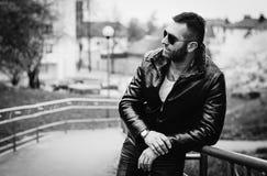 有态度佩带的皮夹克和太阳镜的性感的人 免版税图库摄影
