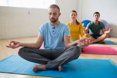 有思考在俱乐部的学生的瑜伽辅导员 图库摄影