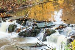 有急流的小河在秋天公园,长的曝光 免版税库存图片