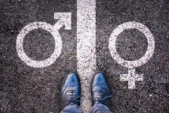 有性别标志的腿在沥青 库存图片