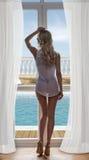 有性感的女用贴身内衣裤的女孩在窗口附近 免版税库存照片