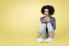 有性感的看起来的少妇指向您的黄色背景的 免版税库存图片