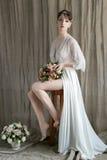 有性感的短发的早晨美丽的精美新娘有一件小花圈丝绸内衣的坐与婚礼花束的一把椅子 库存照片