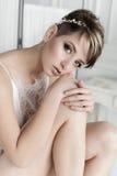有性感的短发的早晨美丽的精美新娘有在他的头的一个柔和的小的花圈的在白色丝绸女用贴身内衣裤在w坐 免版税库存图片