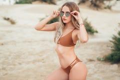有性感的身体的美女在摆在沙滩的棕色泳装 库存照片