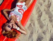 有性感的年轻冲浪者女孩在性感的适合身体比基尼泳装和sunglass 免版税库存照片
