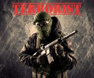 有恐怖分子标志的危险被掩没的和武装的人在脏的bac 库存照片