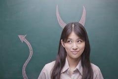 有恶魔垫铁和尾巴的少妇在黑板 库存照片