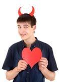 有恶魔垫铁和心脏的少年 库存照片