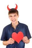 有恶魔垫铁和心脏的少年 免版税库存图片