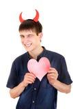有恶魔垫铁和心脏的少年 免版税图库摄影