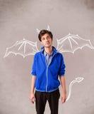 有恶魔垫铁和翼画的年轻人 免版税库存照片
