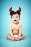 有恶魔垫铁的小滑稽的婴孩 库存照片