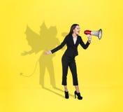 有恶魔阴影的女实业家在后面后 免版税图库摄影