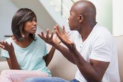 有恼怒的夫妇在沙发的争执 库存图片