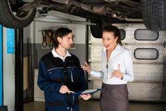 有恼怒的女性顾客的汽车修理师 免版税库存图片