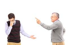 有恼怒的成熟的人与一个更加年轻的翻倒人的一个论据 免版税库存照片