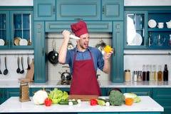 有恼怒的面孔的人厨师与刀子切了胡椒 免版税库存图片