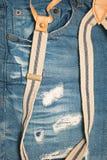有悬挂装置的蓝色牛仔裤 库存照片