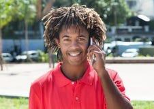 有惊人的发型的非裔美国人的人在电话 免版税库存照片