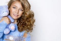有惊人的头发的逗人喜爱,美丽的白肤金发的女孩,拿着玩具熊 库存照片