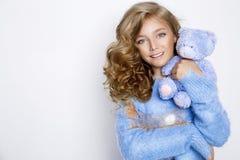 有惊人的头发的逗人喜爱,美丽的白肤金发的女孩,拿着玩具熊 免版税库存图片