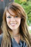 有惊人的微笑的愉快的年轻深色的妇女 免版税库存照片