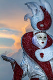 有惊人的服装的迷人的执行者在日落的威尼斯狂欢节期间 免版税库存照片