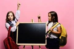有惊奇的面孔的女孩握有的手指想法 佩带书包的孩子在黑板倾斜,复制空间 库存照片
