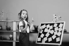 有惊奇的面孔的女小学生在有稠粘的笔记的教室关于黑板 有的女孩想法拿着桃红色铅笔 孩子和 库存照片