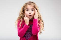 有惊讶神色的逗人喜爱的小女孩  免版税库存照片